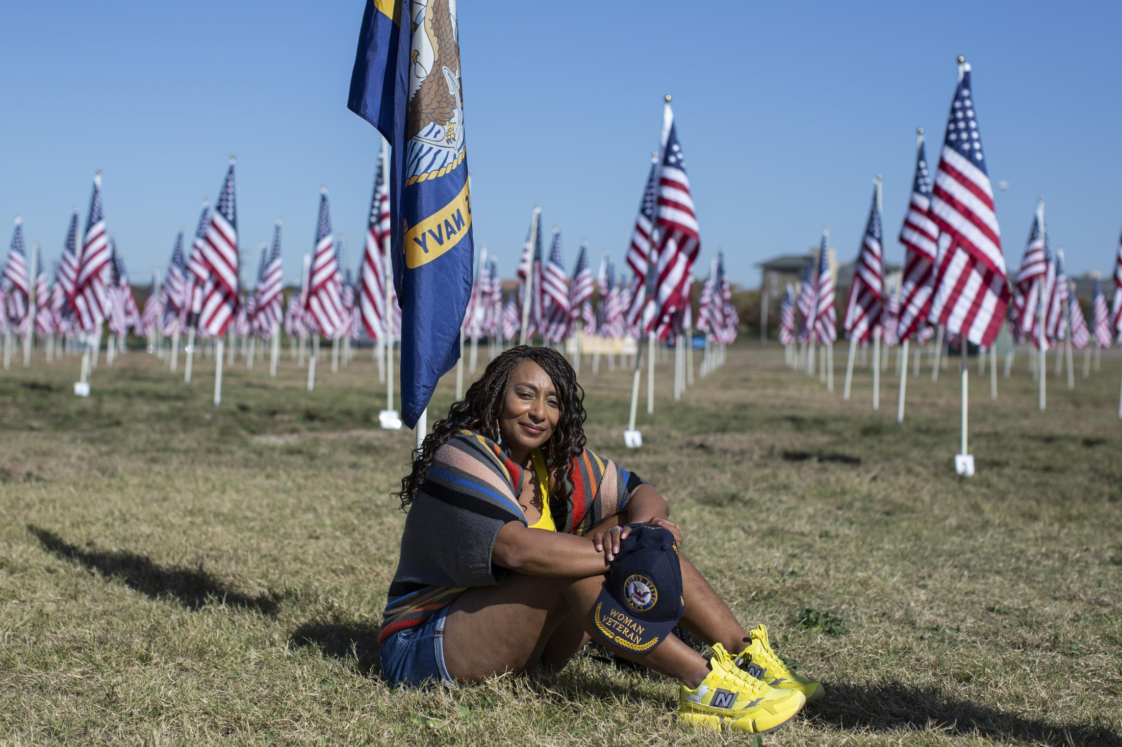 Mary Wilkins, a Veteran of the United States Navy, Sits under the Navy flag at a Veterans Day Memorial in Plano, Texas. Remembering the brave women who have served our country. In 1917 Loretta Walsh became the first woman to enlist in the United States Military, this lead to a 1948 law that made American women an important part of our military. Today 14% of our Active duty military are women and 18% are made up of our reserve and guard forces.