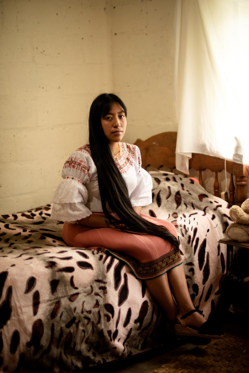 """Katherine Pupiles (20) poses for a portrait into her bedroom. She is a communitarian teacher and physiology student at Quito University. She back to the San Clemente community when the COVID-19 pandemic began. She is one of the five youth indigenous that opened a communitarian education space into the school. As a physiology student, her motivation is to help the children grow up in a healthy environment. """"They made me feel good with them, they transmit me beautiful happiness, it is not possible explained it in words, they make me feel good, their energy is contagious. I wanted to be with them again"""" . April 2, 2021. San Clemente. Johis Alarcón."""