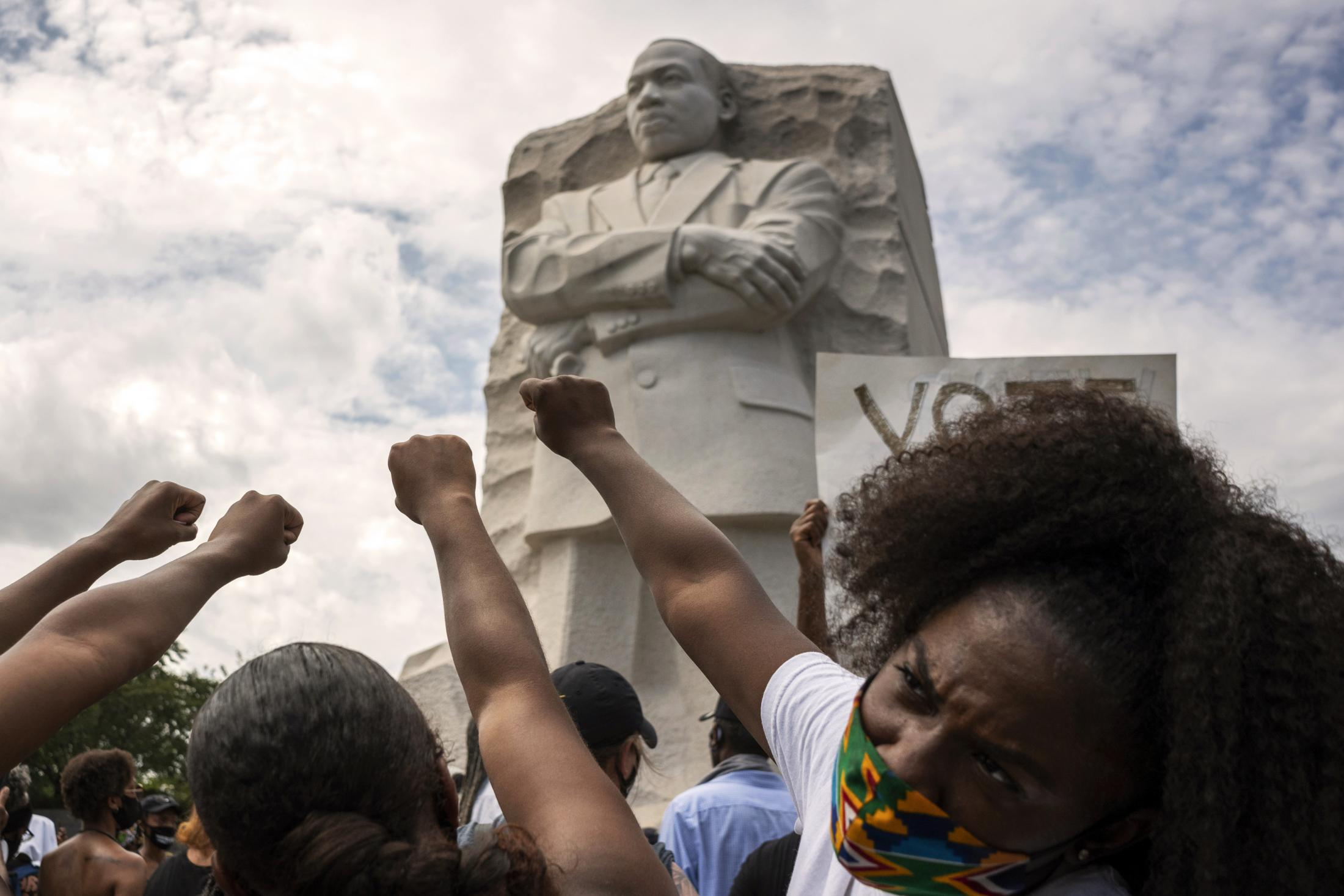 """Black women raise their fists in front of the MLK Memorial during the 57th annual March on Washington, Friday, August 28, 2020 in Washington, D.C. , Maryland. Also referred to as the """"Get Off Our Necks"""" march, this year's march focused on the recent Black Lives Matter movement while commemorating the work of previous civil rights leaders."""