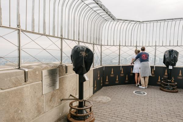Couple enjoying a view on the 86th floor open-air observatory at the Empire State Building