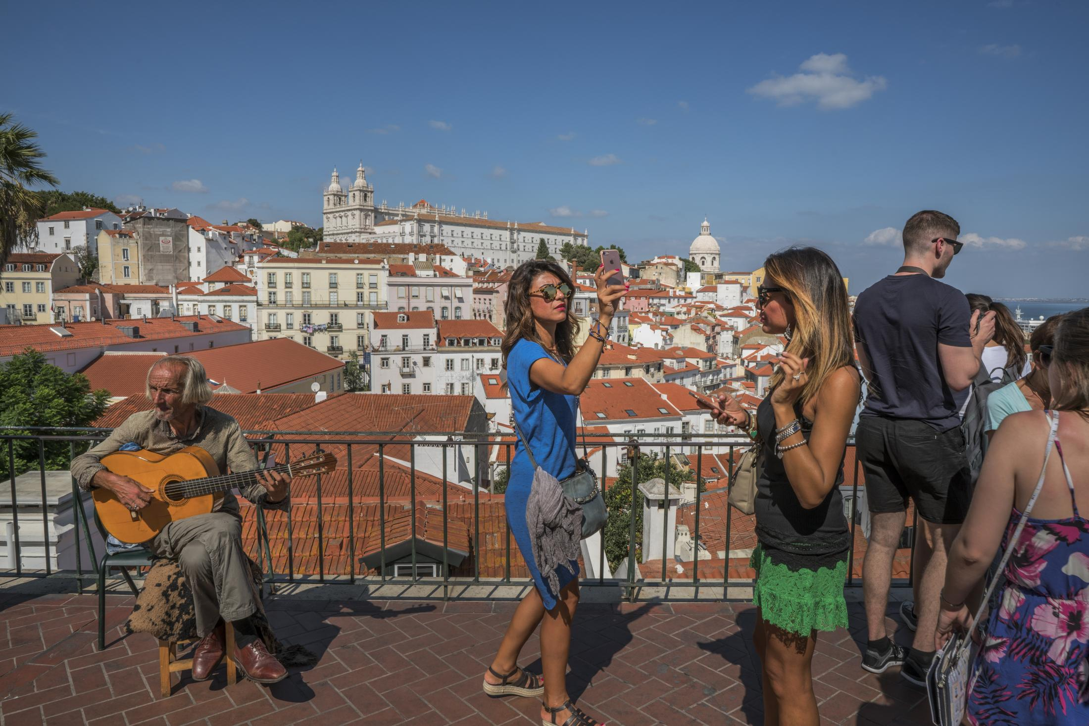 Tourists in Alfama, a historic working class neighborhood in Lisbon that became one its most popular touristic destinations. Several longtime residents of the area, most elderly and poor, are being evicted from their homes so landlords can rent their apartments on Airbnb. Booming tourism has been the engine of Portugal's economic recovery of recent years after an economic crisis in 2008 devastated its economy. The sector today employs 12,4% pf the population os Lisbon and brough in € 8 billion to the city's economy in 2015