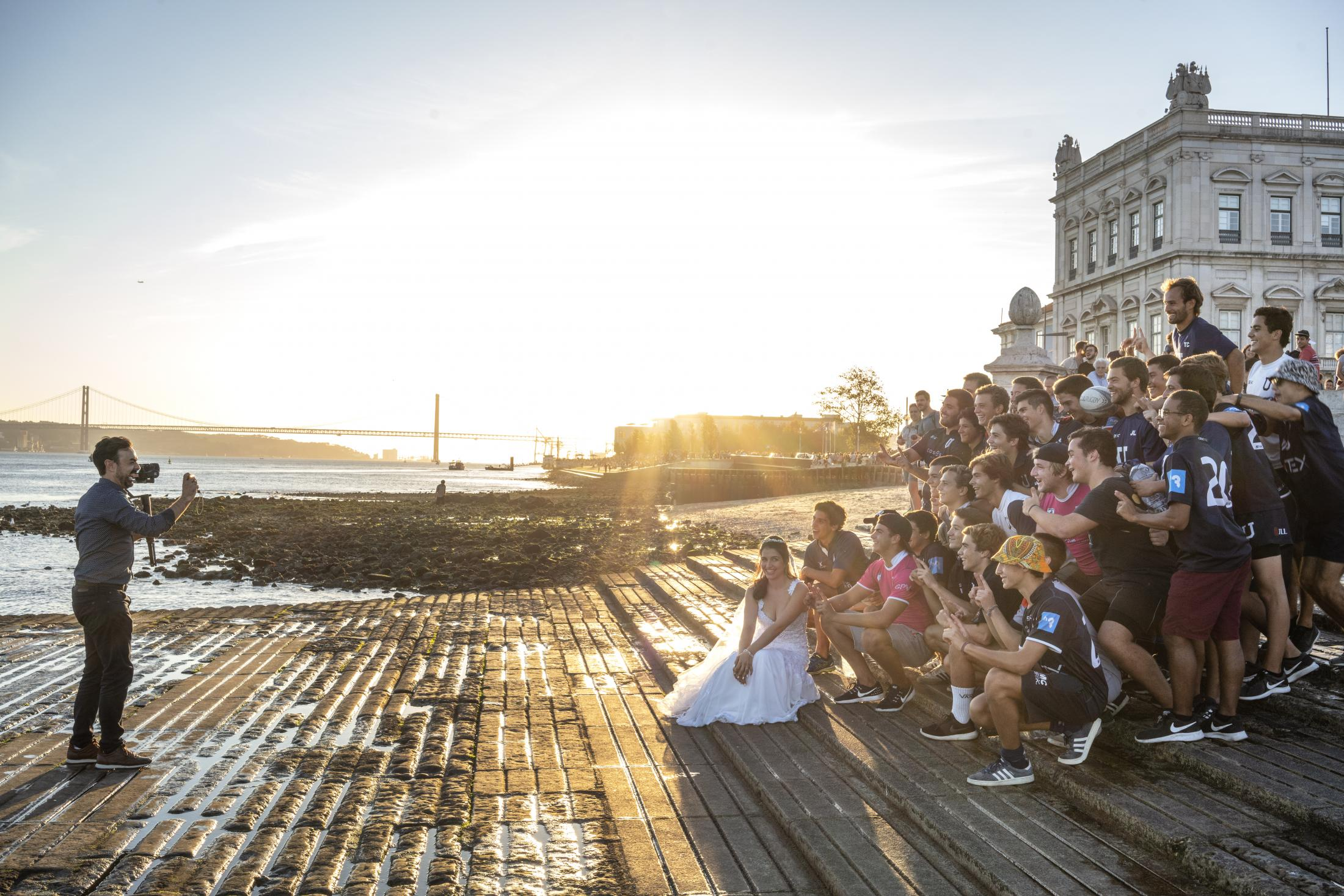 A casual encounter between a bride making pictures for her wedding and a visiting rugby team at the Cais das Colunas in the Baixa area of Lisbon
