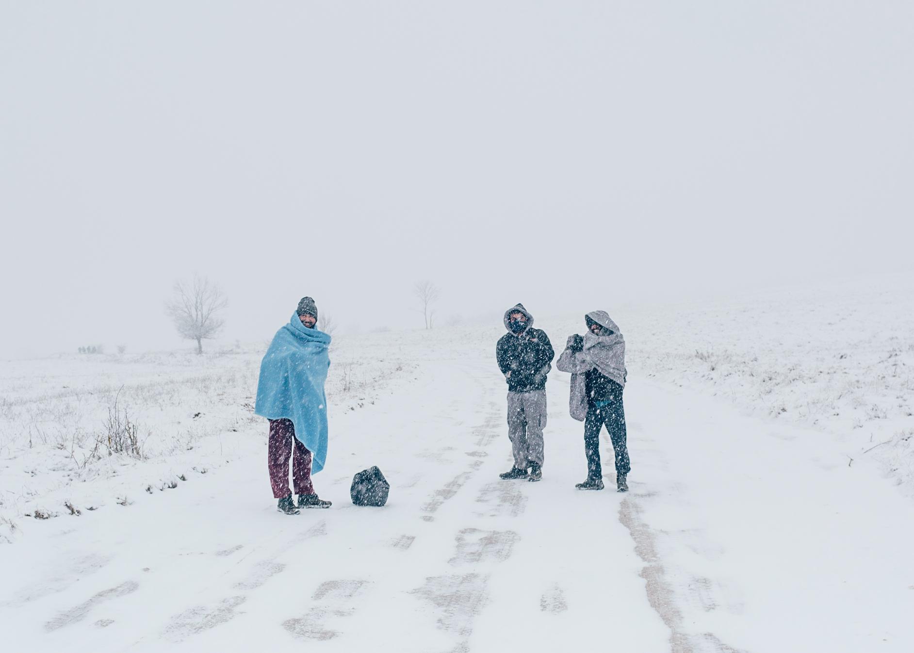 Migrants walk walk in the snow close to former camp Lipa.