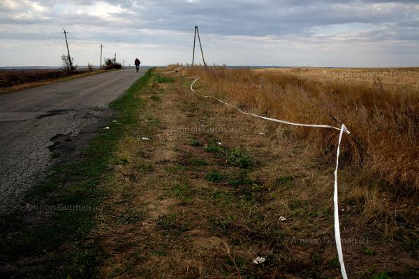 A man passes by the remains of Malaysia Airlines Flight 17 (MH17), near Hrabove village, Donetsk Oblast. it was a scheduled passenger flight from Amsterdam to Kuala Lumpur that was shot down on 17 July 2014 while flying over eastern Ukraine, killing all 283 passengers and 15 crew on board.