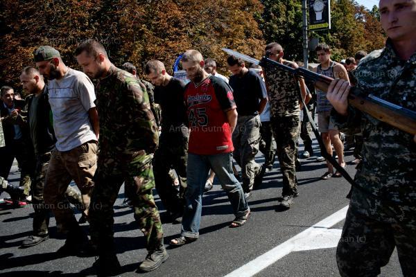 Donetsk people's militia man, escorts captured Ukrainian army prisoners, in the central square of Donetsk, eastern Ukraine.