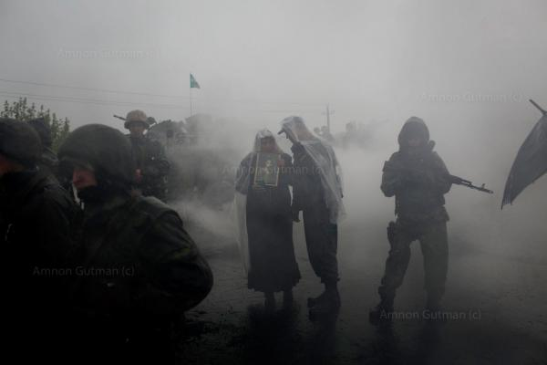 A woman who supports Russia and a Ukrainian Army commander take cover from the rain while Pro Russia civilians block the road in the village of Andreevka, 10 km south of Slavyanks.