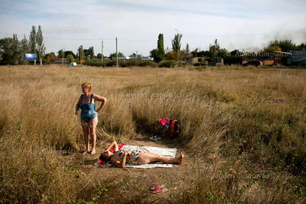 Residents of Slovyanks, a city that was under control of Donetsk people's militia, and was captured by the UA army, taking a rest during a hot summer day.
