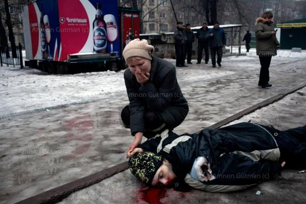 A mother hold her son's hand while mourning his death, after a grad rocket attack in a residential area of Donetsk.