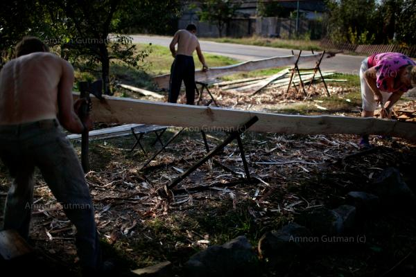 Residents of Slovyanks, a city that was under control of Donetsk people's militia, and was captured by the UA army, fixing their house which was destroyed by shelling.