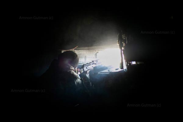A Ukrainian soldier open fires towards no man's land in between DPR and UA forces, after a diversion group of DPR soldiers was spotted moving around.