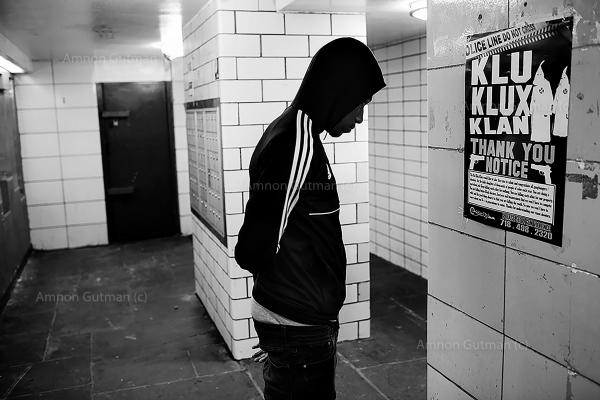 """A resident of Linden houses reads a sign the was put by ManUp Inc in the building entrance: """"The KKK would like to take this time to salute and congratulate all gangbangers/shooters, for the daily slaughter of thousands of people of colour each year. you are doing a marvellous job. keep killing each other for nothing......"""""""