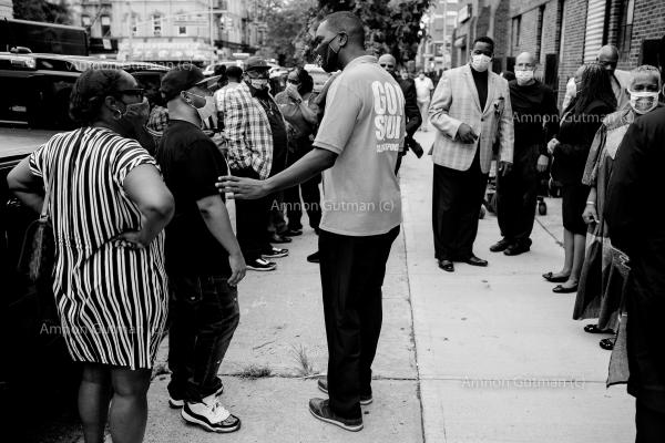 Pastor Gilford Monrose, the founder of the God Squad (a local grassroot organisation, helping the community to confront gun violence), comforts a family member of a 60 years old man who was shot and killed inside a church. Bedford Stuyvesant, Brooklyn.