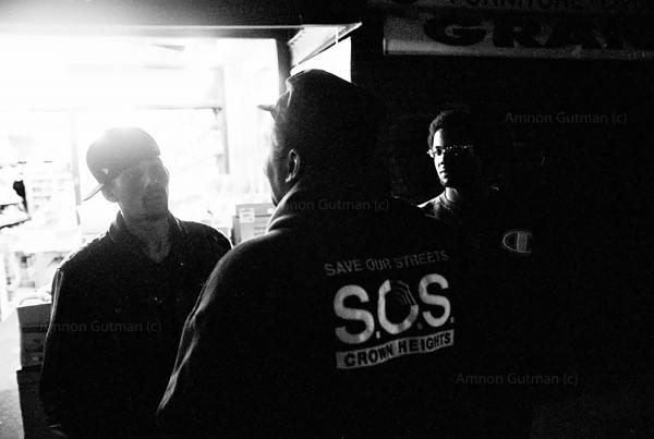 S.O.S outreach team member talking to young adults, during one of his night walks in the neighborhood of Crown Heights.