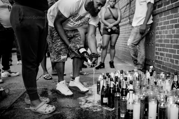 """Community members pour champagne on the sidewalk to honor and remember Spooky, a 41 year old man that was shot dead in Flatbush, he left a young son. """"Innocent people were shot, and it looks like it's gang-related, and we have to work together to be able to identify the perpetrators; """"I need people to come forward,"""" said the police detective who is in charge of the investigation."""