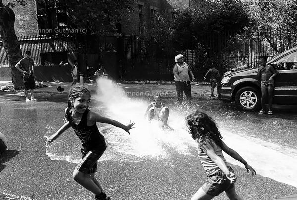 Children playing with a water hose during a hot spring day, in Crown Heights.