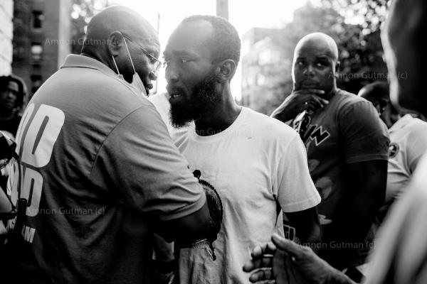 """Pastor Matthiew (L) of the God Squad (a local grassroot organisation, helping their community to confront gun violence), comforts members of the family of """"Spooky"""" , a 41 year old man, was shot dead in Flatbush .""""Innocent people were shot, and it looks like it's gang-related, and we have to work together to be able to identify the perpetrators; I need people to come forward,"""" said the police detective who is in charge of the investigation."""