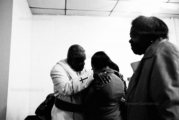 Reverend Kevin Jones of Peterson Temple Ministries comforts one of his congregants during a Sunday church service. Jones began the Clergy Action Network and works closely with S.O.S. to help reduce gun violence on the streets of Crown Heights.