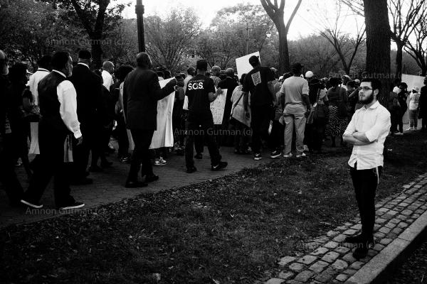 An orthodox Jew watches over as a peace march organized by S.O.S is moving though Eastern Parkway, after 94 people were killed in Crown Heights since the beginning of 2015 as a result of crime in the community.