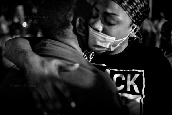 During an Occupy Corner event in Flatbush organized by The God Squad and East Flatbush Village, Ticia Smith (L) is comforted by a member of her community after telling the story of her brother's murder.