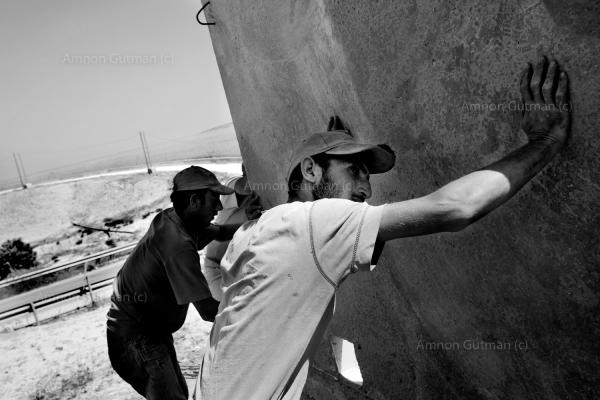 Palestinians who work and stay legally in Israel, helping build parts of the new fence, where the1967 border line was. The 5 kilometres area of the 1967 line fence just outside Ar Ramadin village is notoriously easy to slip through. South Mt Hebron, Israel.