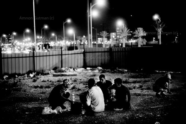 A group of Palestinians teenagers, who stay and work illegally in Israel. having dinner at one of the many spots where they sleep at night. Beer-Sheva City,
