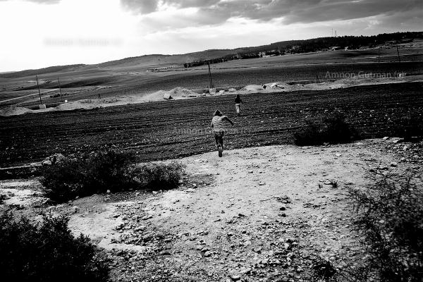 A Palestinian kid, running towards what used to be the 1967 border line between Israel and Jordan (now West Bank), in order to cross into Israel. South Mt Hebron, West Bank.