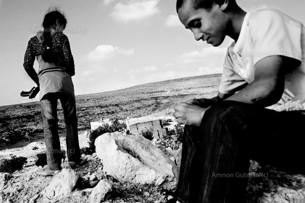 """Children from Ar Ramadin village, looking at Palestinians who cross back """"illegally"""" into the West Bank, after a working week in Israel, at the outskirts of Ramadin village. The 5 kilometres area of what used to be the 1967 border line fence just outside the village was notoriously easy to slip through. in 2017, Israel finished constricting the barrier in those 5km."""