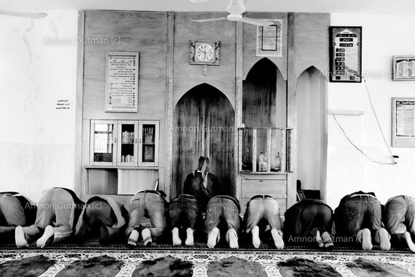 Bedouin men from Ar Ramadin tribe, praying in the village mosque. a destruction notification from the Israeli authorities on the pretext of illegal building of the mosque, was issued. The notification was over thrown after the Sheikh of the village talked to the Israeli authorities. Ar Ramadin Village, South Mt Hebron, West Bank.