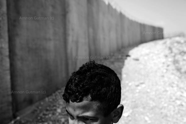 A Child from Ar Ramadin tribe playing alongside the new separation barrier wall that was built right in front of his family house. Ar Ramadan village, South Mt. Hebron. West Bank.