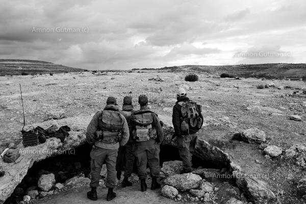 Israeli soldiers looking towards Ar Ramadin village, while guarding the new fence being built behind them, eventually the separation barrier wall was completed in 2017 in that area.