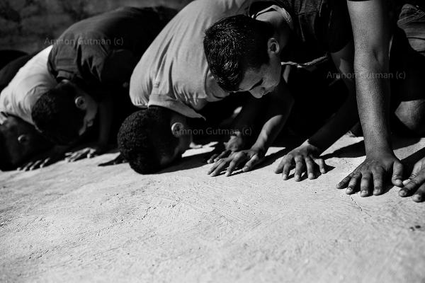 Members of Ar Ramadin tribe praying outside one of the village mosques, a destruction notification from the Israeli authorities on the pretext of illegal building of the mosque, was issued. Eventually the Sheikh of the village was able to push back the warrant, by talking to the Israeli authorities and the mosque remained in place. Ar Ramadin Village, South Mt Hebron, West Bank.