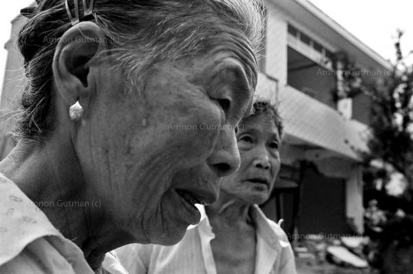 Zhang Hongxu (Left) and her husband Wejingline, both survived the quake, waiting for food distribution , near the ruins of their home, Xiangwang village, Sichuan province.