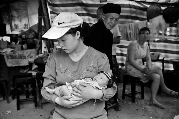 A baby who was born one week after the 7.8 magnitude quake, carried by his mother at the family shelter, Leigu town.