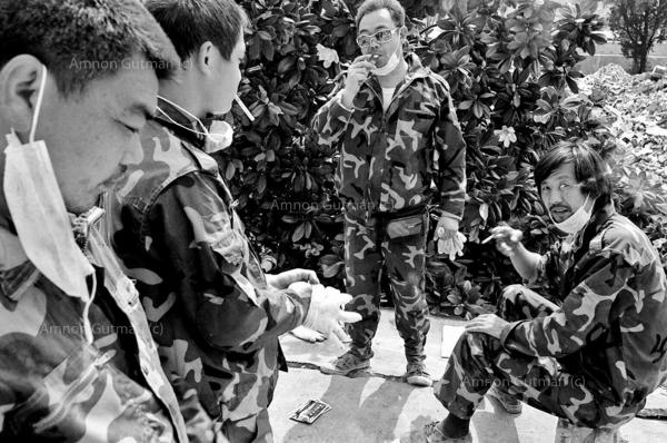 Residents taking a smoke break, while salvaging their belongings at the destroyed town of Yingxiu. over half of the towns population of 10000 have died in the quake.