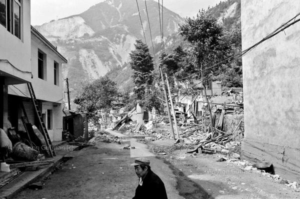 A quake survivor sitting outside his destroyed home and shop, waiting for soldiers to come and help him clear rubble from his house. Yingxiu town, Sichuan province.