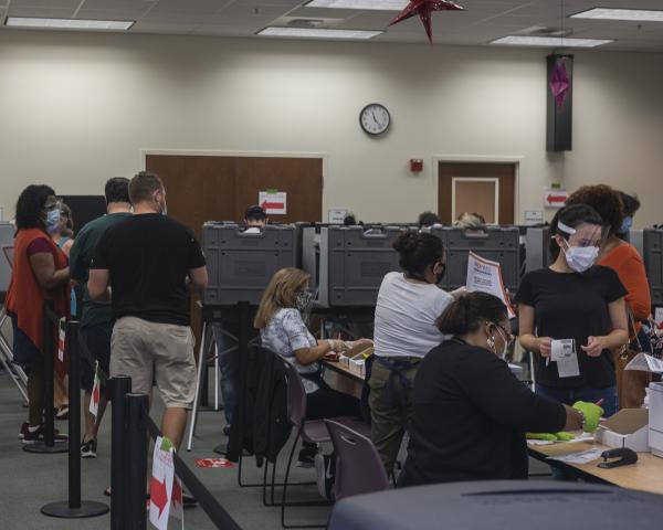 Weston, Fl – October 29, 2020: Early voters waiting their turn to vote and checking in with poll workers inside of the Broward County Library Weston Branch - an early voting location. Credit: Andres Guerrero