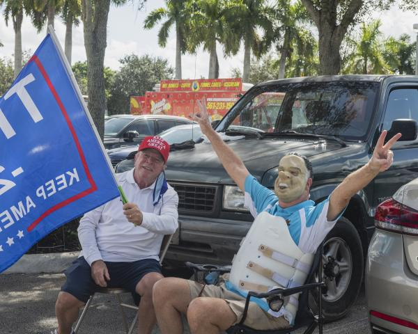 Weston, Fl – October 29, 2020: Larry and Tom (with Nixon mask) sitting in the parking lot of the Broward County Library Weston Branch - an early voting location. Credit: Andres Guerrero