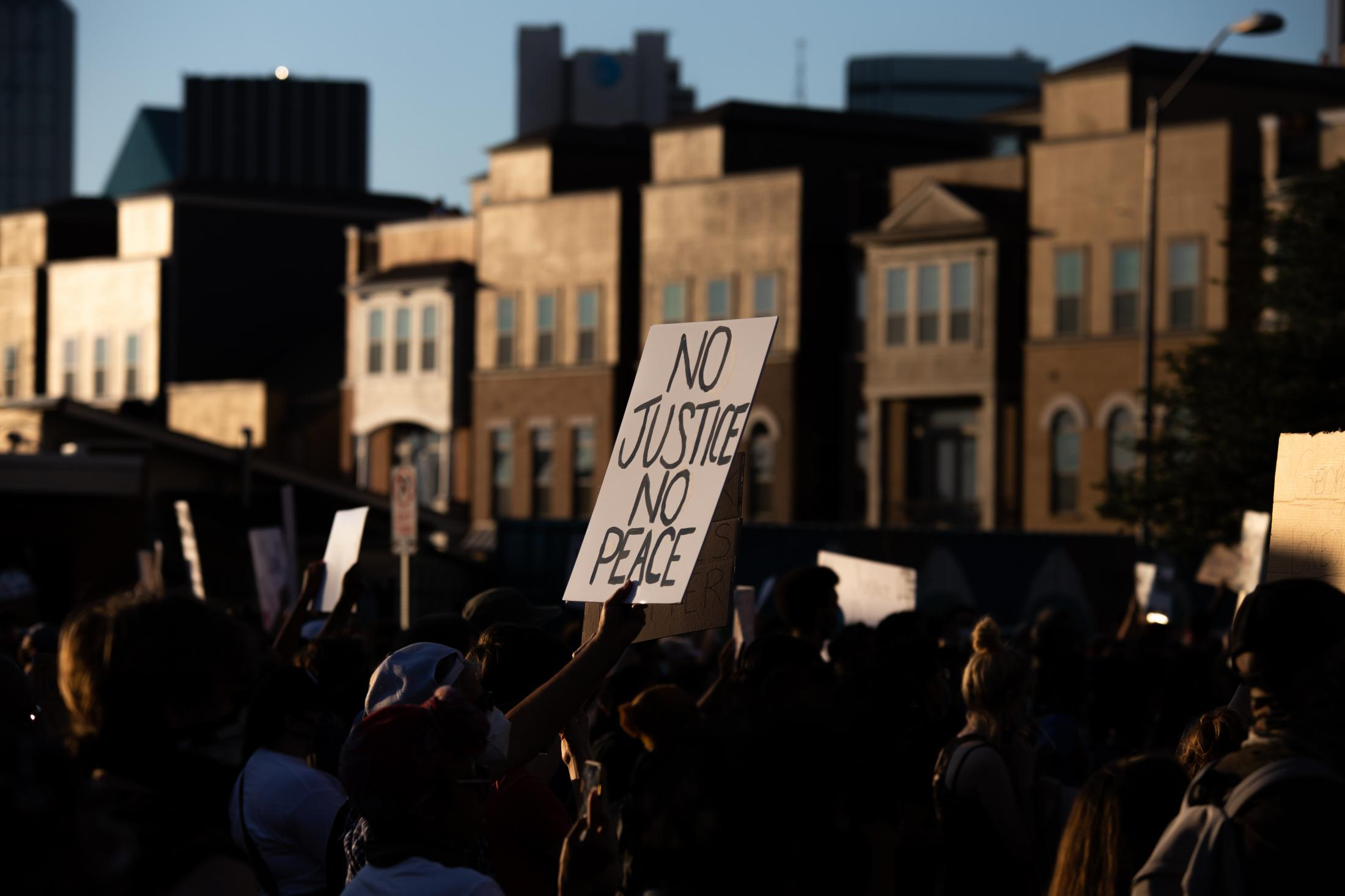 """A sign that reads """"No Justice, No Peace"""" is held up high during the march of police killings. No justice, No peace, has been used from many demonstrations to express that there will be no peace on the streets if there is no justice for Black Americans' murder."""