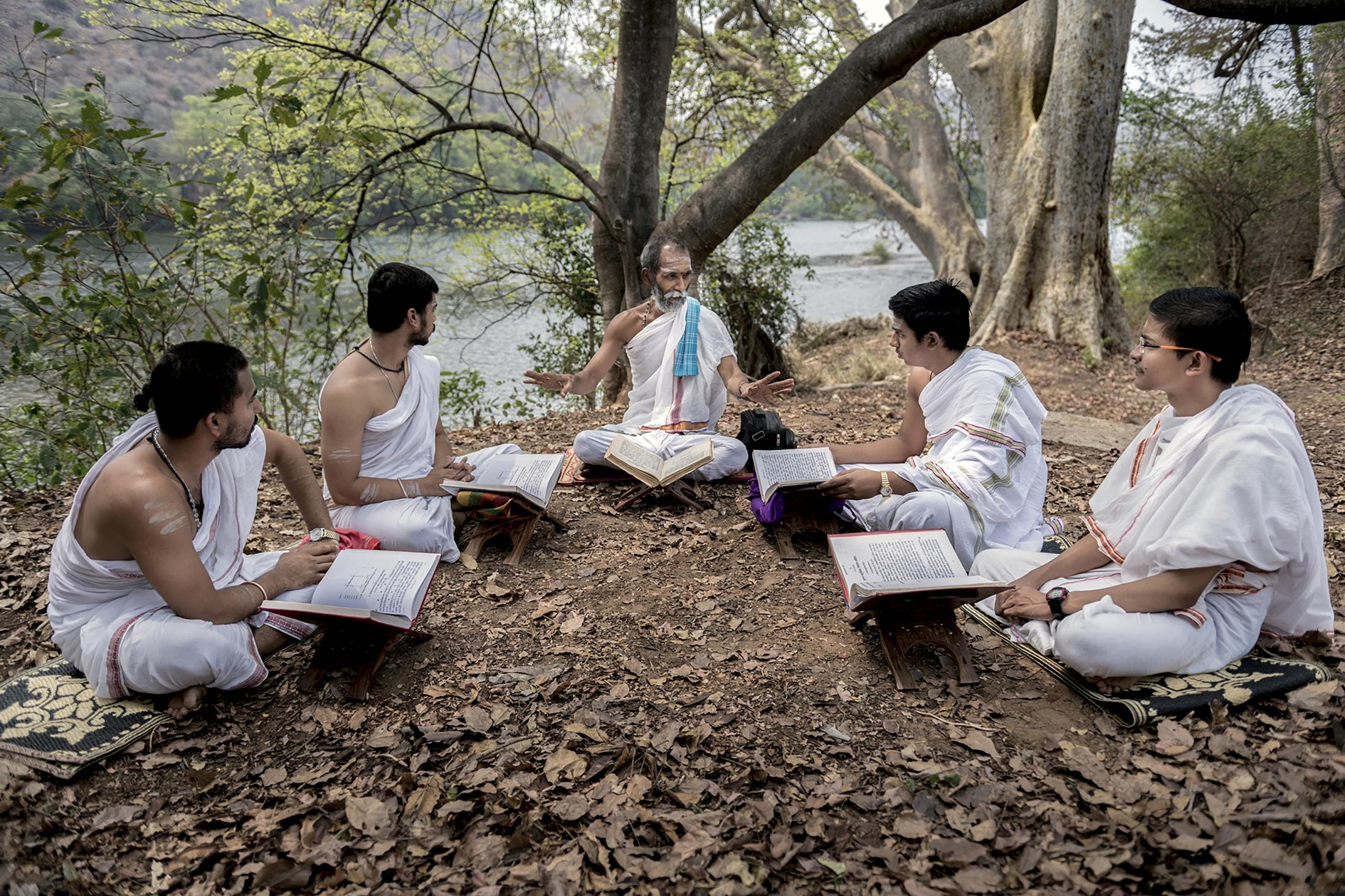 Vedic Guru teaches Yajurveda to senior students of Gurukula. The early Vedic teachers attached great importance to studying under trees.