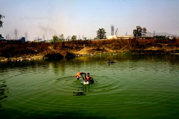 Children playing in a water dump at the village of Sarayplay, which borders the main steel plant in Raigrah city, Chhatisgrah, India.