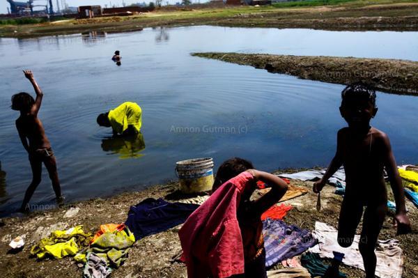 Children searching for fish, near the main steel plant, which borders their village- Kiromal Nagar, Chhatisgrah.