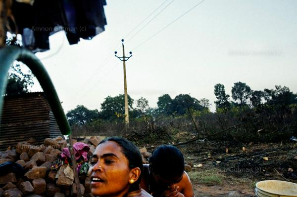 Women taking bath at the living quarters of steel plant workers (manily their husbands) in the village of Tarimal, that borders one of the main sponge plant, in Raigarh district, Chhatisgrah, India.