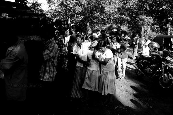 Family members of Sinhalese civilians who were killed by a roadside claymore mine explosion made allegedly by LTTE carders, mourn their loved ones deaths during a mass burial for 26 people killed in the incident. Buttala, South Sri Lanka