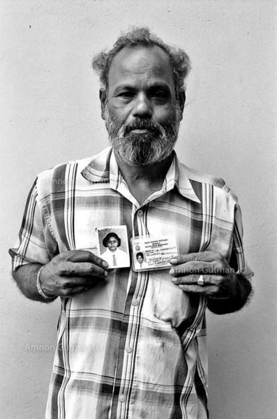 A Tamil man holds pictures of his son and daughter , who were abducted by unknown assailants during the conflict. Trincomalee, East Sri Lanka.