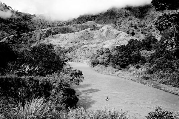 Matigasalug Manobo man crosses a river on his way back home, Mindanao.