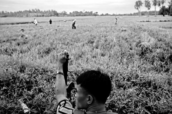 Rodel Cantomayor (c) guarding his fellow family members while they work in the fields located at the no mans land area between christian and muslim communities.