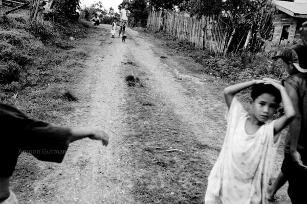 Children waiting for their parents to return from the family fields, located at the no mans land area between christian and muslim communities.