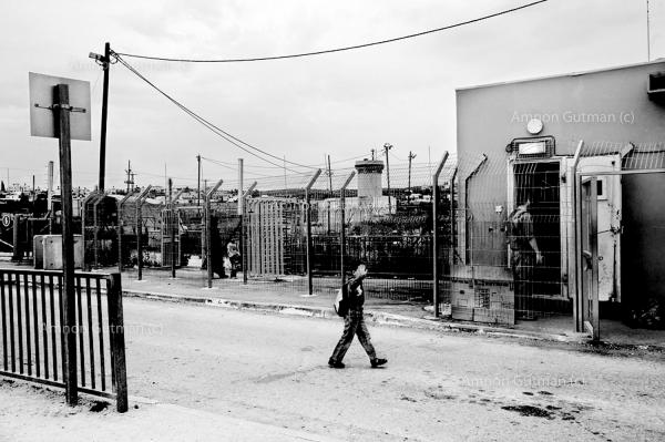 A Palestinian boy crosses over from Israel to the West Bank through an Israeli checkpoint, as reservists keep watch.