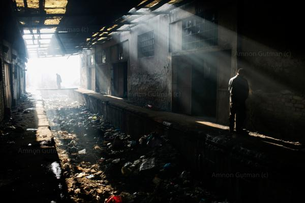 Refugees standing between two abandoned warehouses, where they sleep in, at the back side of Belgrade train station.