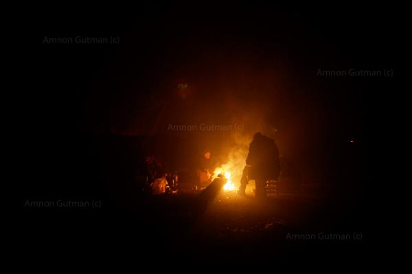 Refugees warming themselves by a fire,  inside a warehouse where they sleep in, at the back side of belgrade train station.